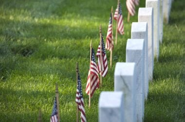american flags in front of tombstones at AHRQ7GY scaled