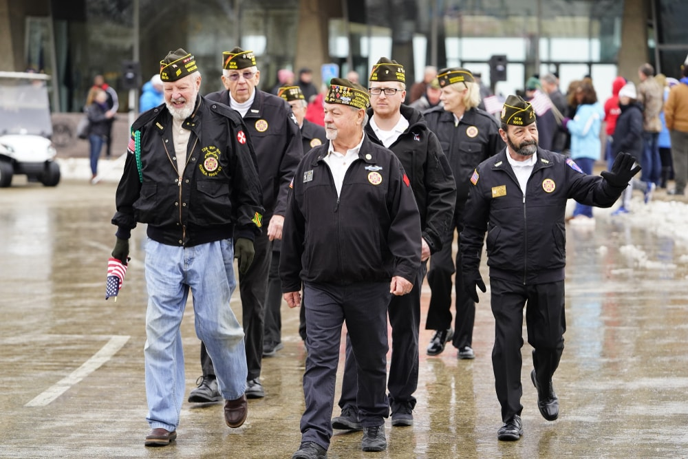 Group of Veterans walking in a parade and waving at their onlookers.