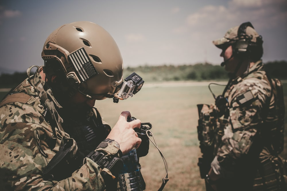 Many active duty service members (shown here) joining the civilian workforce later may continue working with 100% VA disability rating. One examines a camera, one looks out into the distance.