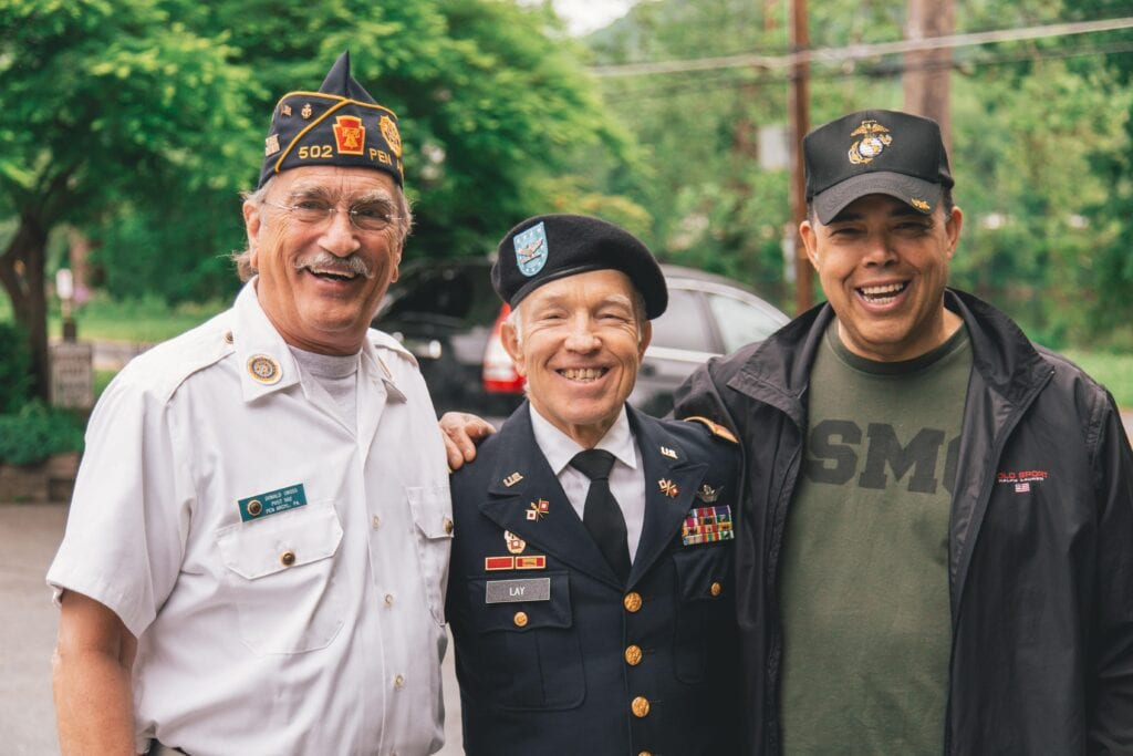 Far from being Veterans in crisis, a group of three Veterans smile at the camera.