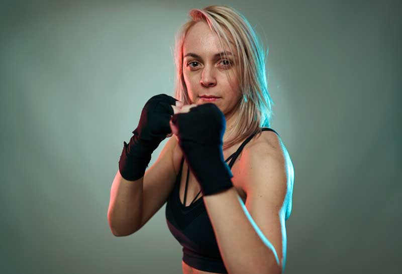 blonde woman with raised, taped fists confidently looks at camera