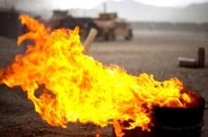 flame from burn pits burns near military vehicles