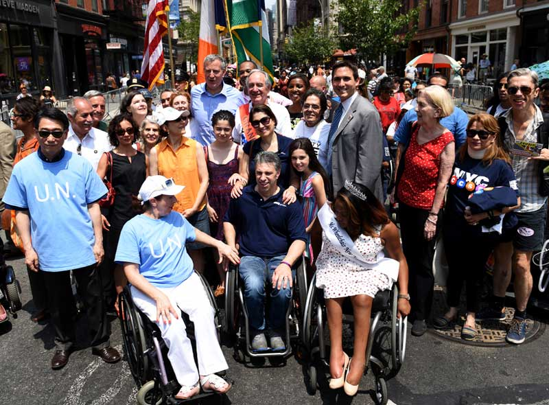 large diverse group of people, some with physical disabilities, smile at the camera