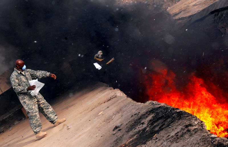 active duty service member wearing mask throwing items into burn pit