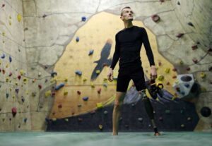 veteran with prosthetic left leg stands in front of rock wall, looks off into distance