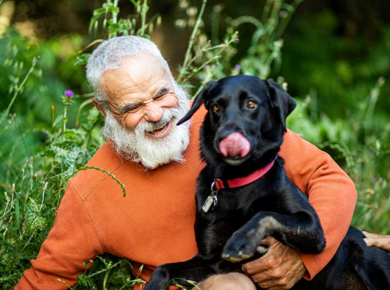 Veteran in field laughs with dog
