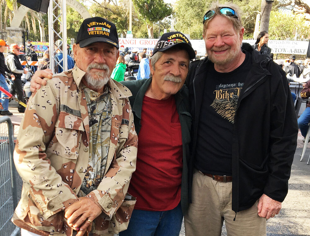 A group of Vietnam Veterans smile at the camera.