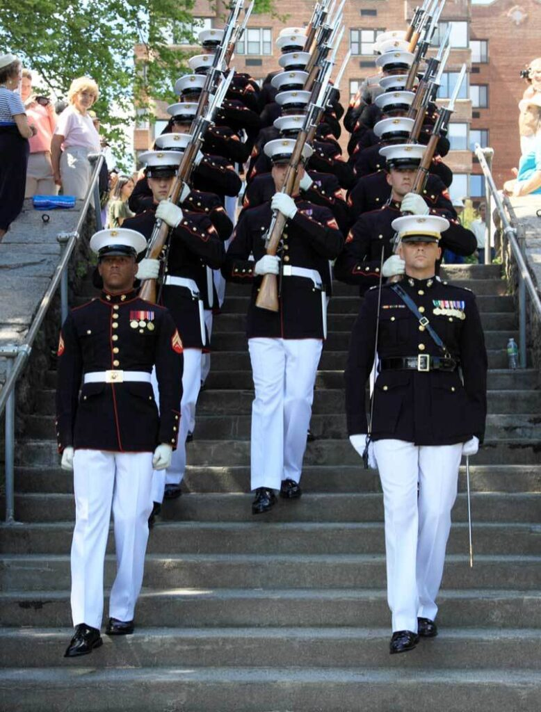 Military servicemen walking uniformly down a set of stairs in an outside setting