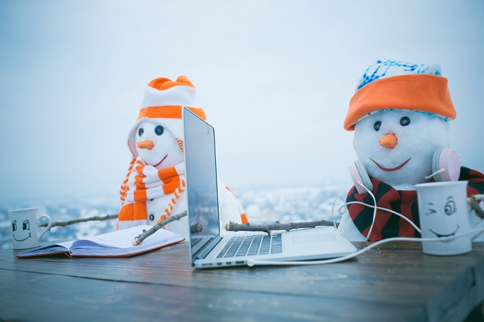 two snowmen, sitting, with laptop book and mugs on a video call with loved ones