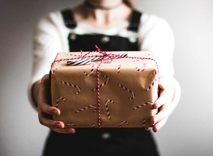 Child offers gift, wrapped in brown paper with candy canes