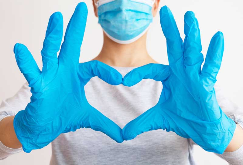 doctor, wearing gloves, making heart with fingers