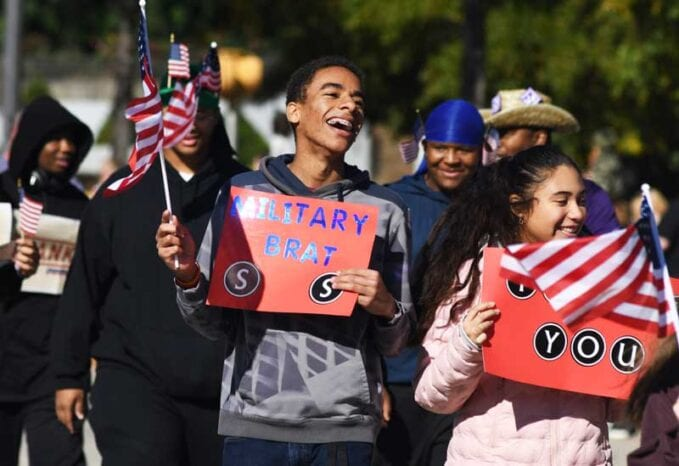 A small group of onlookers positively cheers on Veterans in a parade setting