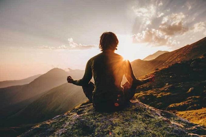 Person meditates on mountain at sunrise