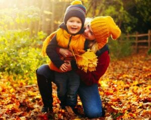 mother and child, smiling and kneeling in autumn leaves