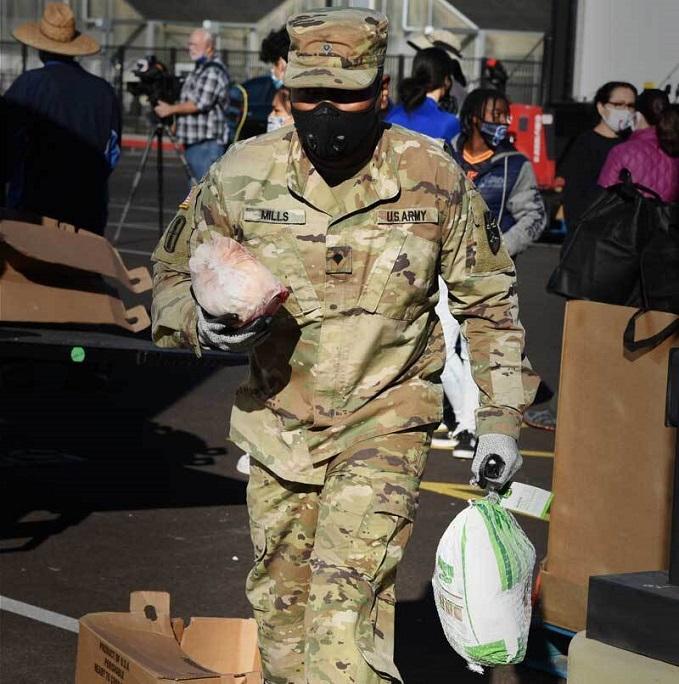 Service member, carrying turkeys, volunteering at food bank