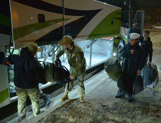 Navy service members load gear on bus