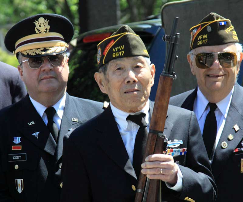 Three Veterans pictured, Veteran in the foreground holding a rifle