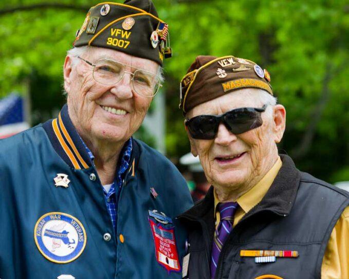 An elderly Korean War Veteran smiles at the camera with a fellow Veteran