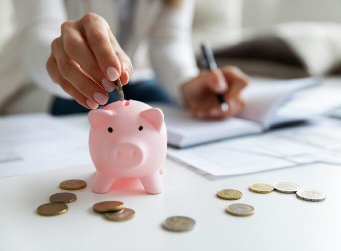 woman puts coins in piggybank
