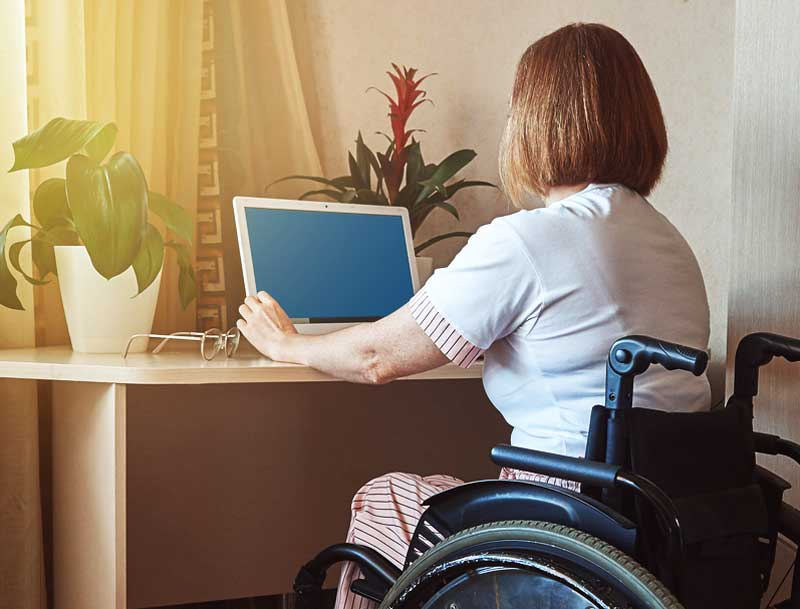 a disabled veteran in wheelchair turns on a tablet at her desk